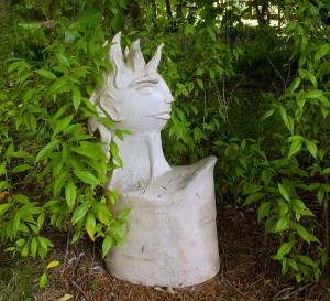 Skulptur im grünen Versteck